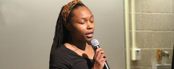 Graduate student Simone Savannah reading poems before the Kevin Powell talk.