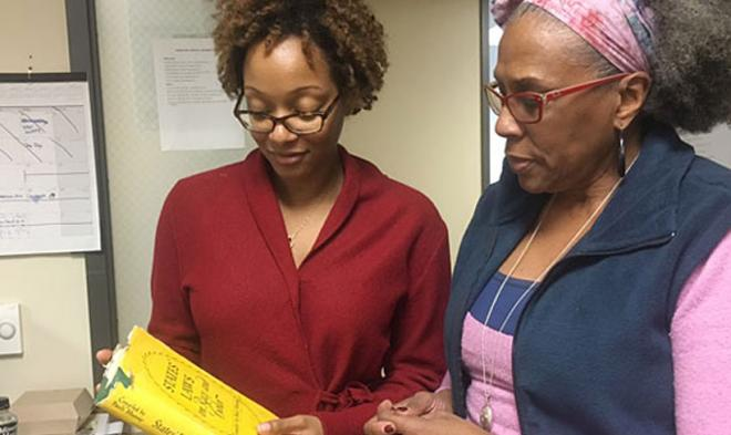 Professor Ayesha Hardison (KU English) and Prof Graham examine a newly acquired rare book by Pauli Murray, States' Laws on Race and Color.